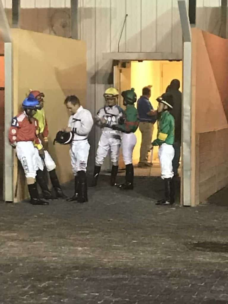 Picture of jockeys waiting to mount their horses for a race.