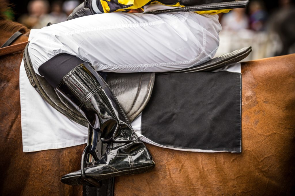 picture of a jockey sitting on a racehorse and there is a weighted pad under the saddle