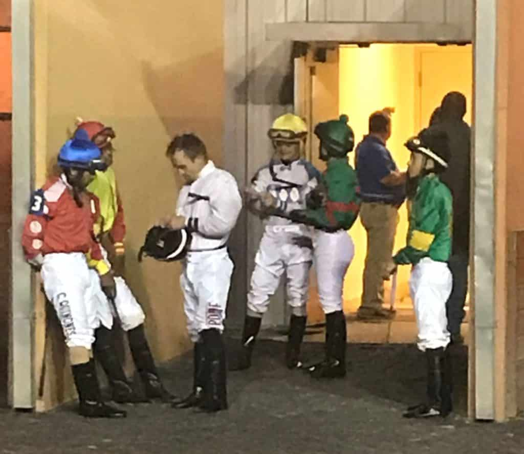 Picture of a group of jockeys waiting to mount their racehorses.