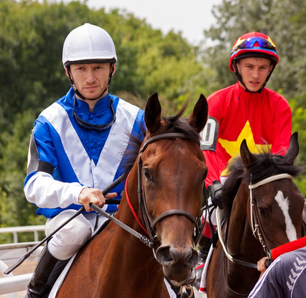 Picture of a jockey holding a whip while sitting on a racehorse.