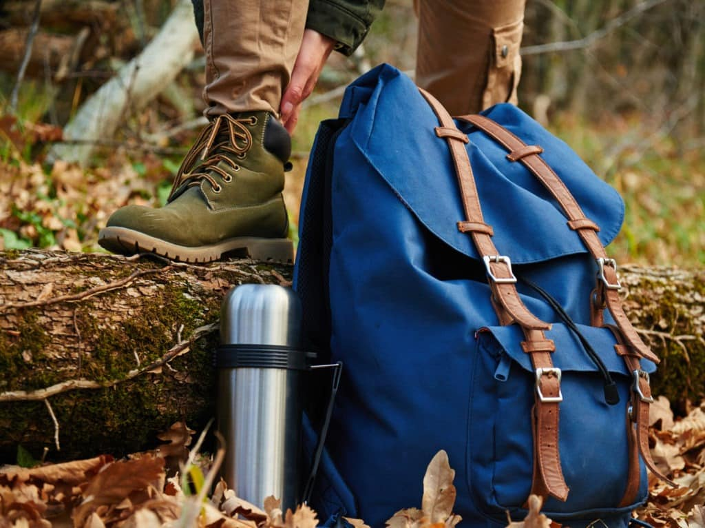 Picture of a person wearing hiking boots with a heel standing on a log.   A backpack and thermos is also in the photo,