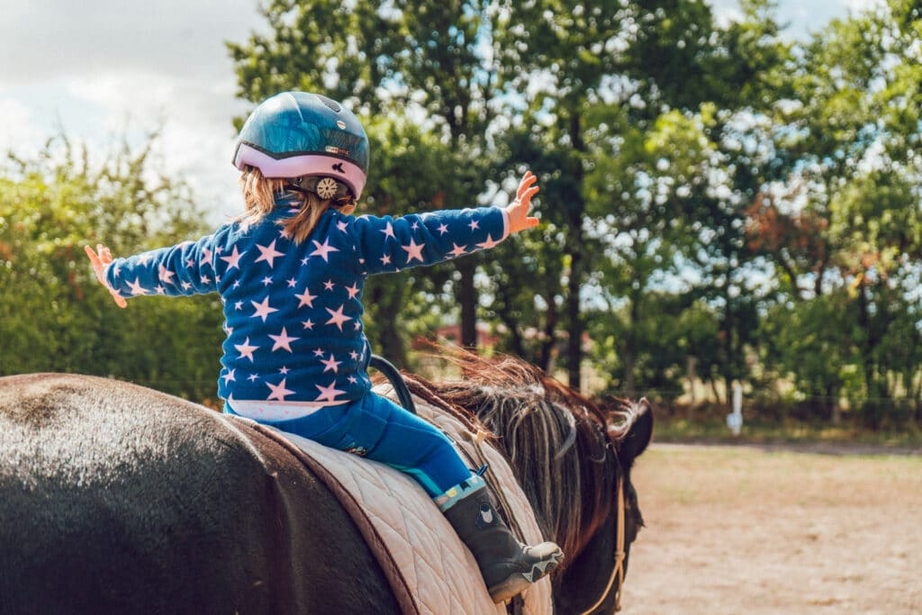 picture of a young child riding a horse with a helmet, but holding her arm dangerously out from her sides,