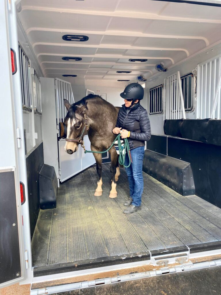 Picture of a woman with her horse inside a horse trailer.