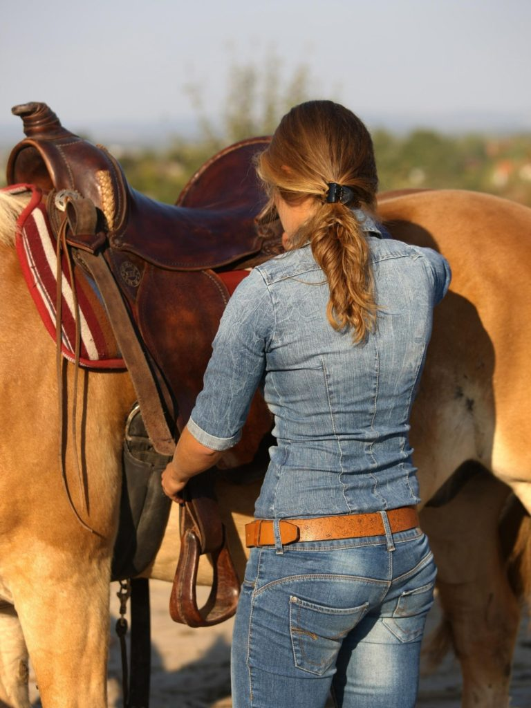 Picture of a woman adjusting the stirrups on her saddle,