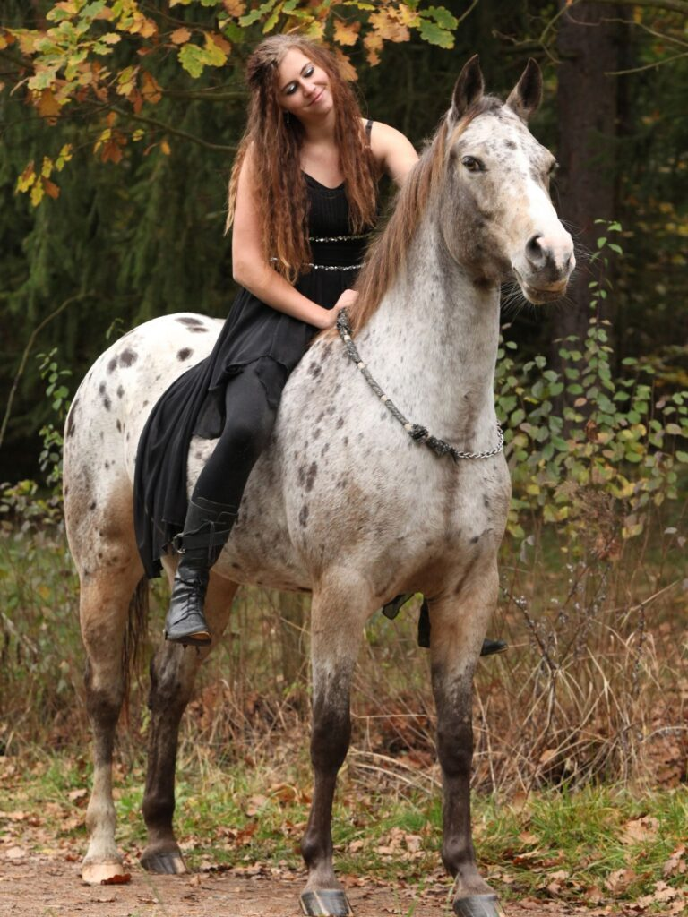 Picture of a woman sitting on her horse and stroking its mane,