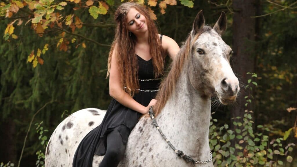 Picture of a woman riding a horse without a bit,