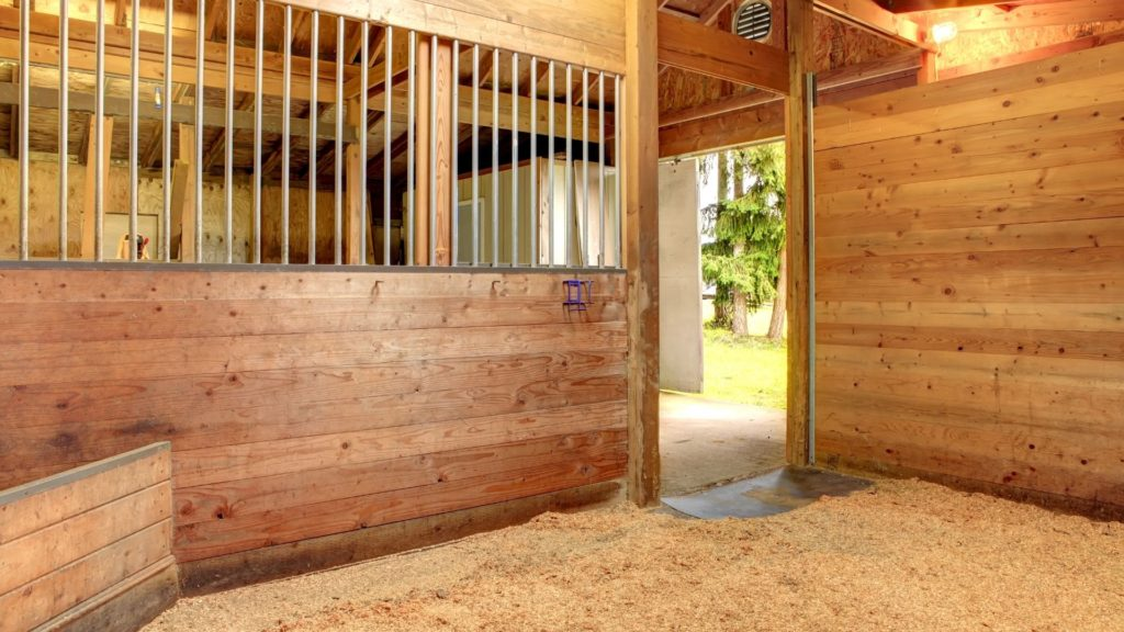 picture of an empty horse stall that shows the barn flooring,