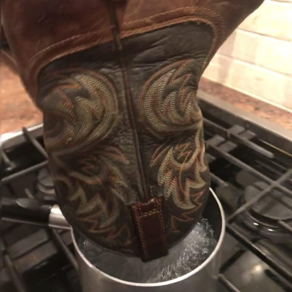 picture of me holding my ariat boots over a pot of boiling water to make them easier to break in and stretch.