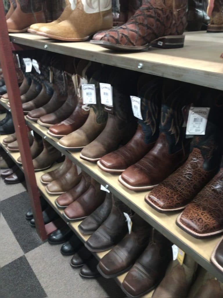 Picture of a rack of cowboy boots, some for men with wide feet or big calves,