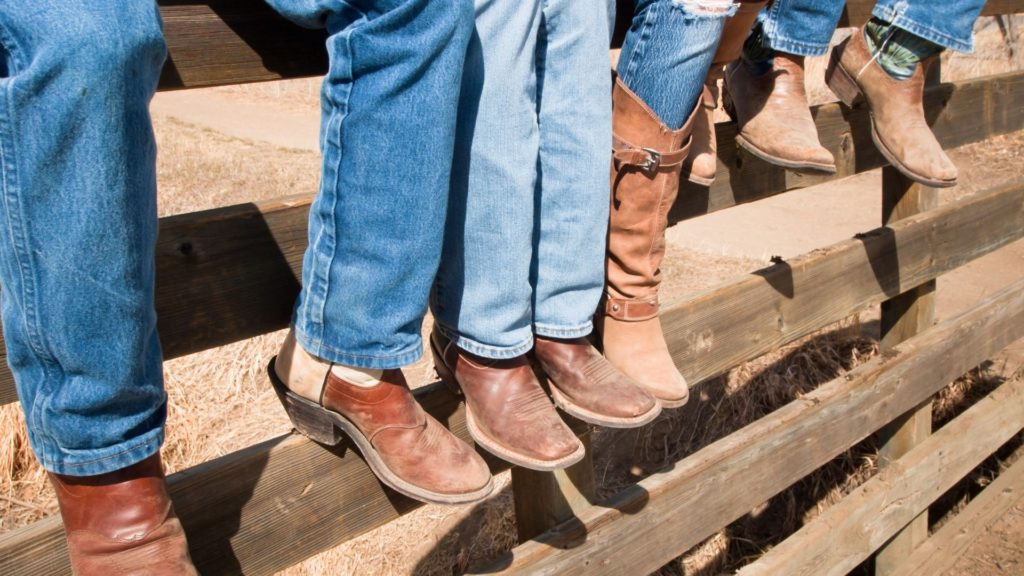 picture of men sitting on a fence wearing cowboy boots on their feet,