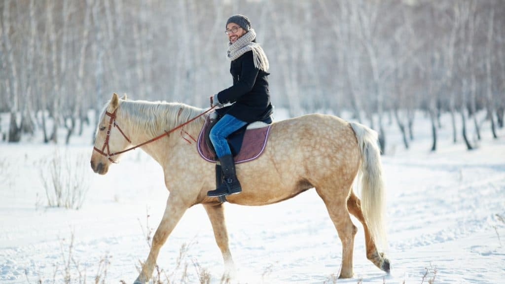 Picture of a woman riding her horse in the winter snow,