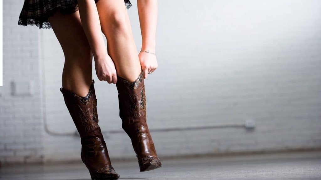 picture of a woman struggling to pull on a cowboy boots,