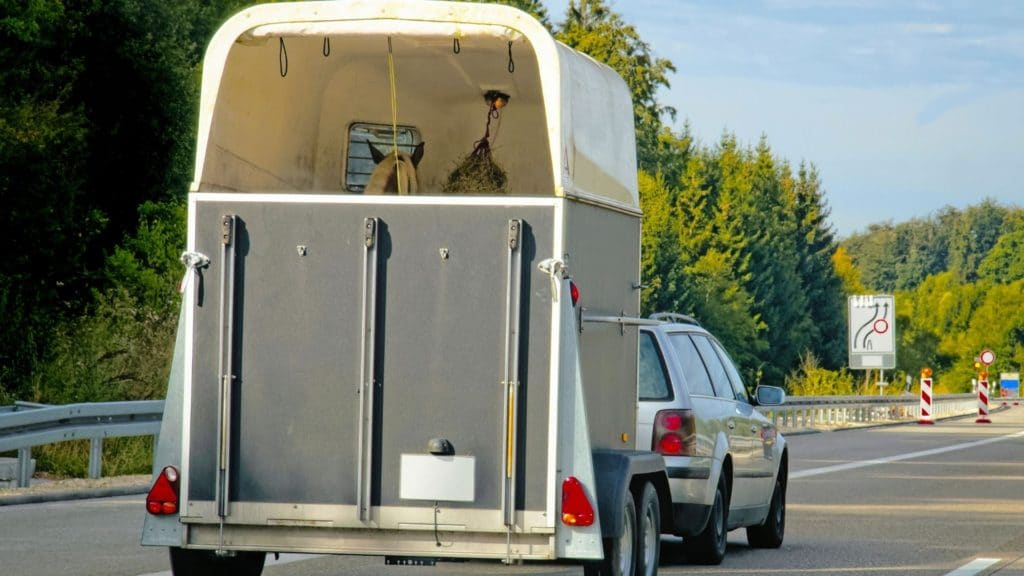 Picture of a station wagon pulling a bumper-pull horse trailer,