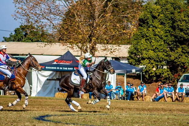 picture of a woman hitting the ball during a polo match,