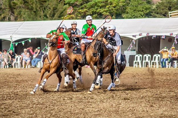 picture of a team playing polo and horses bumping each other,