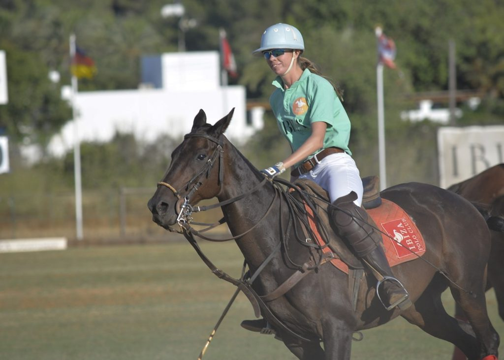 picture of a smiling polo player riding her horse during a match, polo surely doesn't seem like a cruel sport,