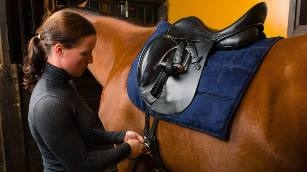 picture of a woman getting her horse ready for a ride,