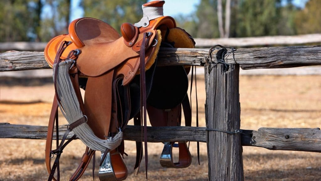 Picture of a western horse saddle sitting on a fence,