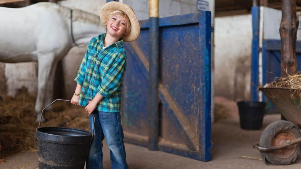 Picture of a child carrying a feed bucket to his horse.