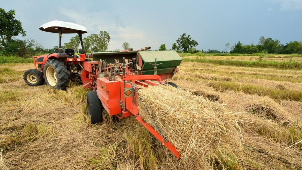 Picture of a tractor and hay baling machine.