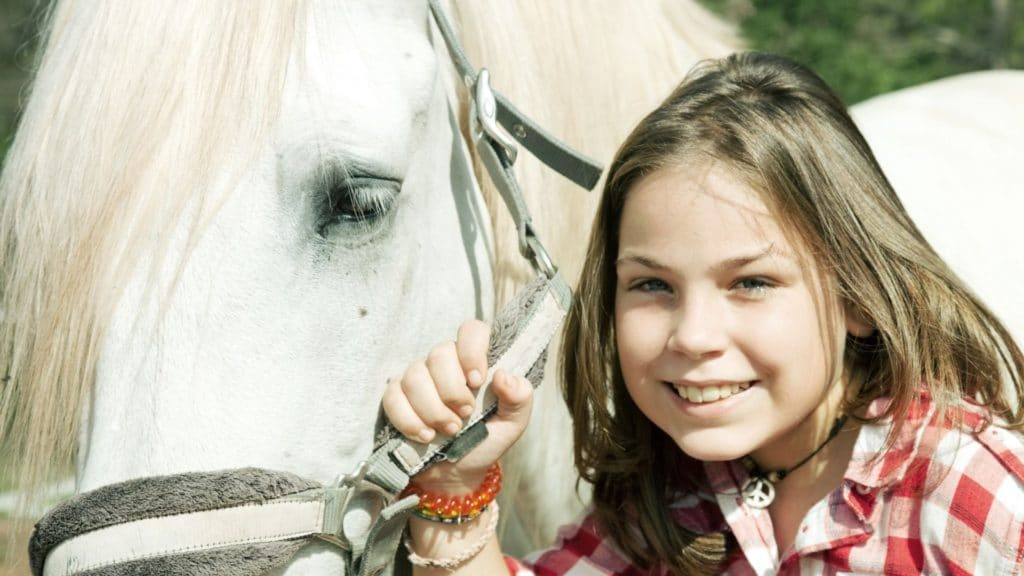 Picture of a girl holding a horse by its halter.