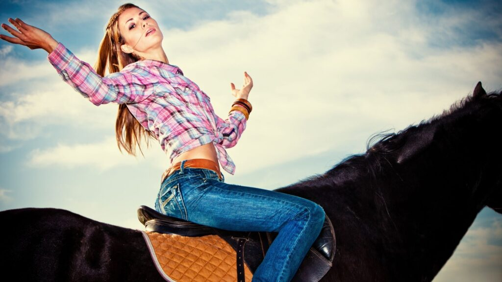 Picture of a woman riding a horse in jeans.