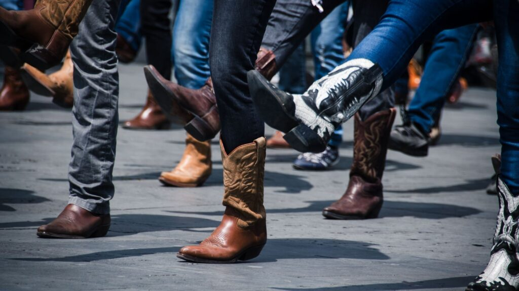 Picture of women wearing jeans and boots dancing.
