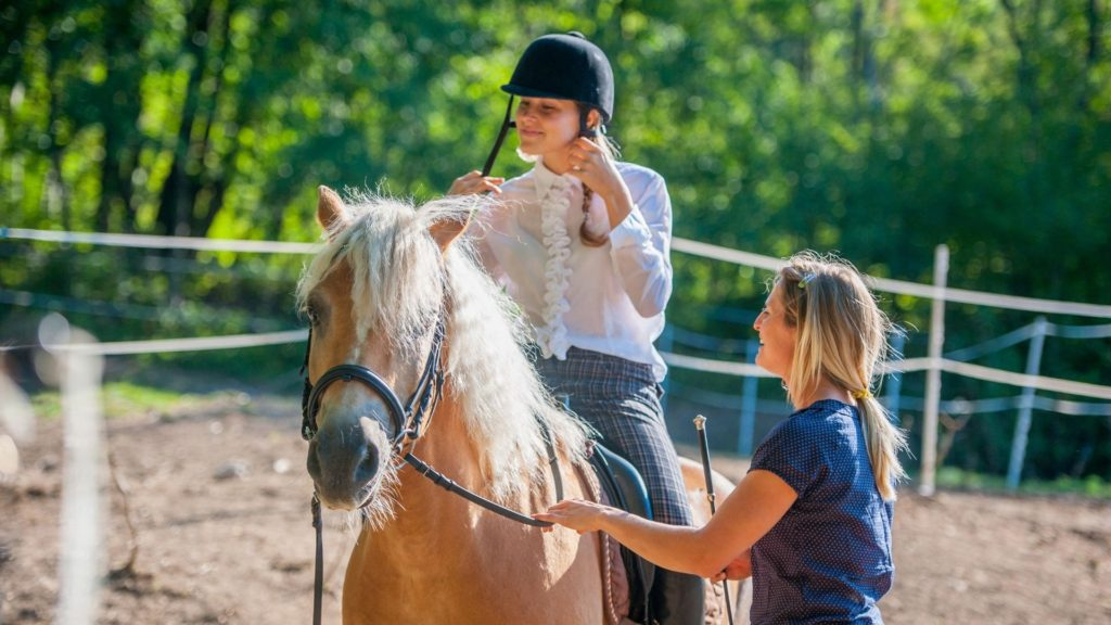 Picture of a young girl getting riding lessons.