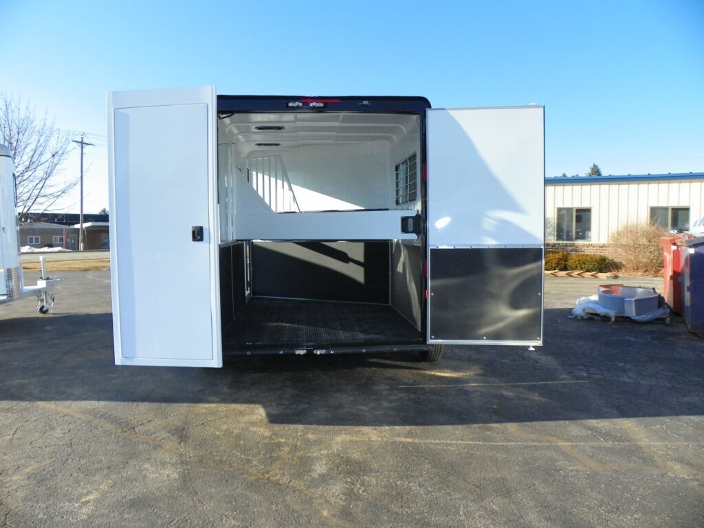 Picture of a bumper-pull horse trailer with its rear doors open showing the dividers,