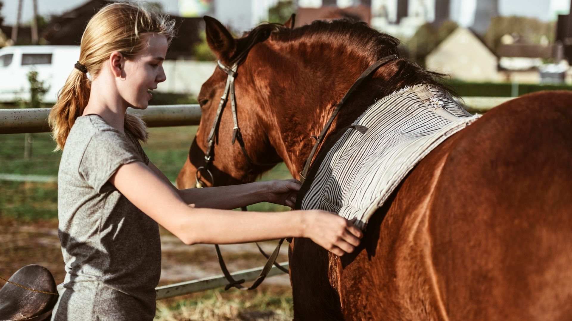 Picture of a girl putting a saddle pad on a horse.