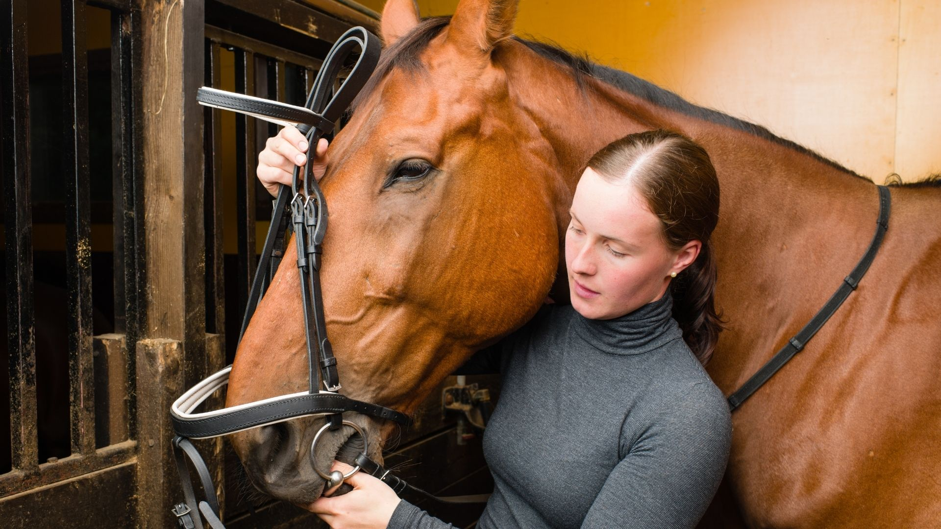Picture of a woman putting a bridle on her horse.