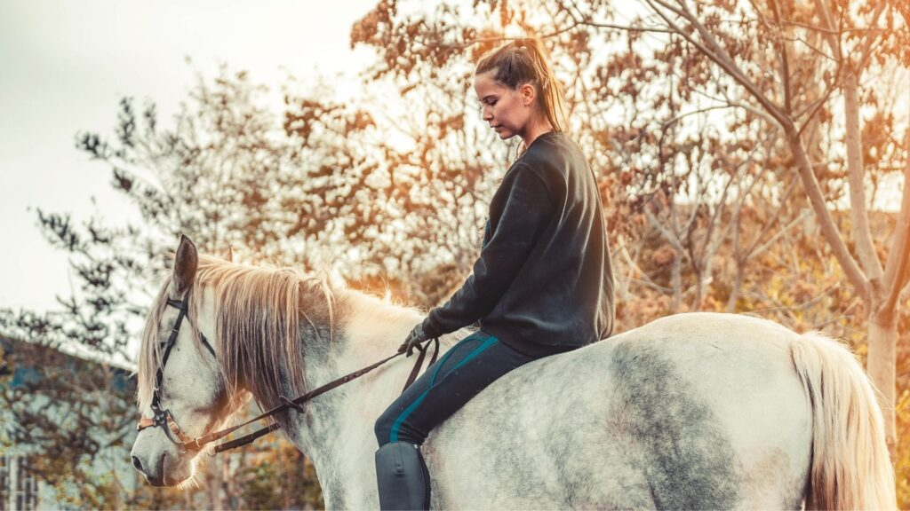 Picture of a woman riding a horse with a hackamore