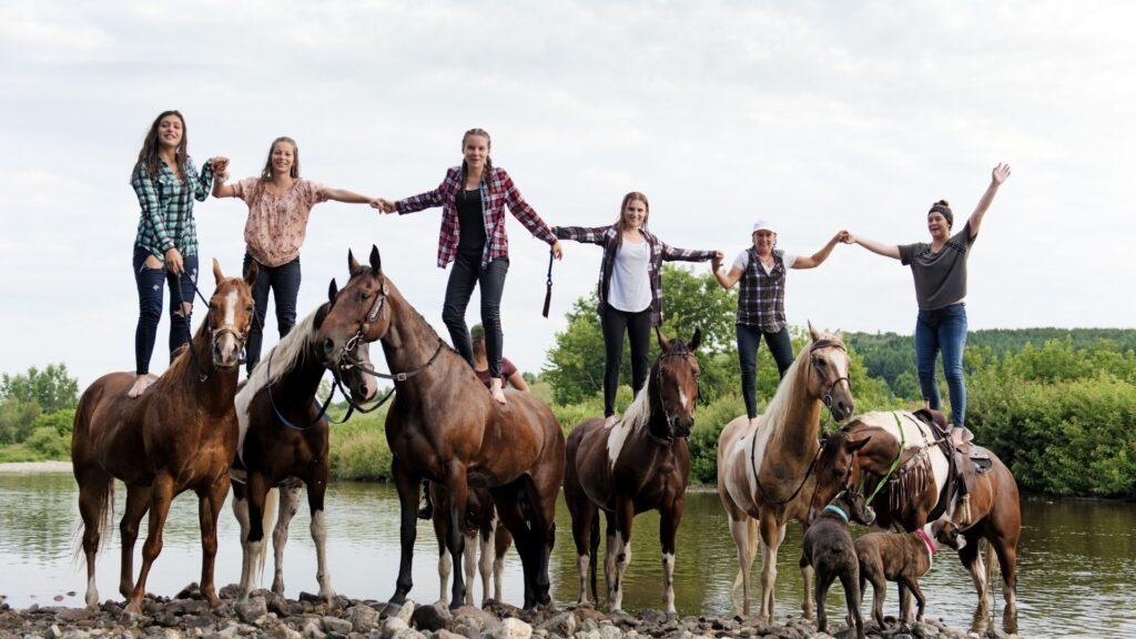 Picture of a group of girls standing on their horses back.