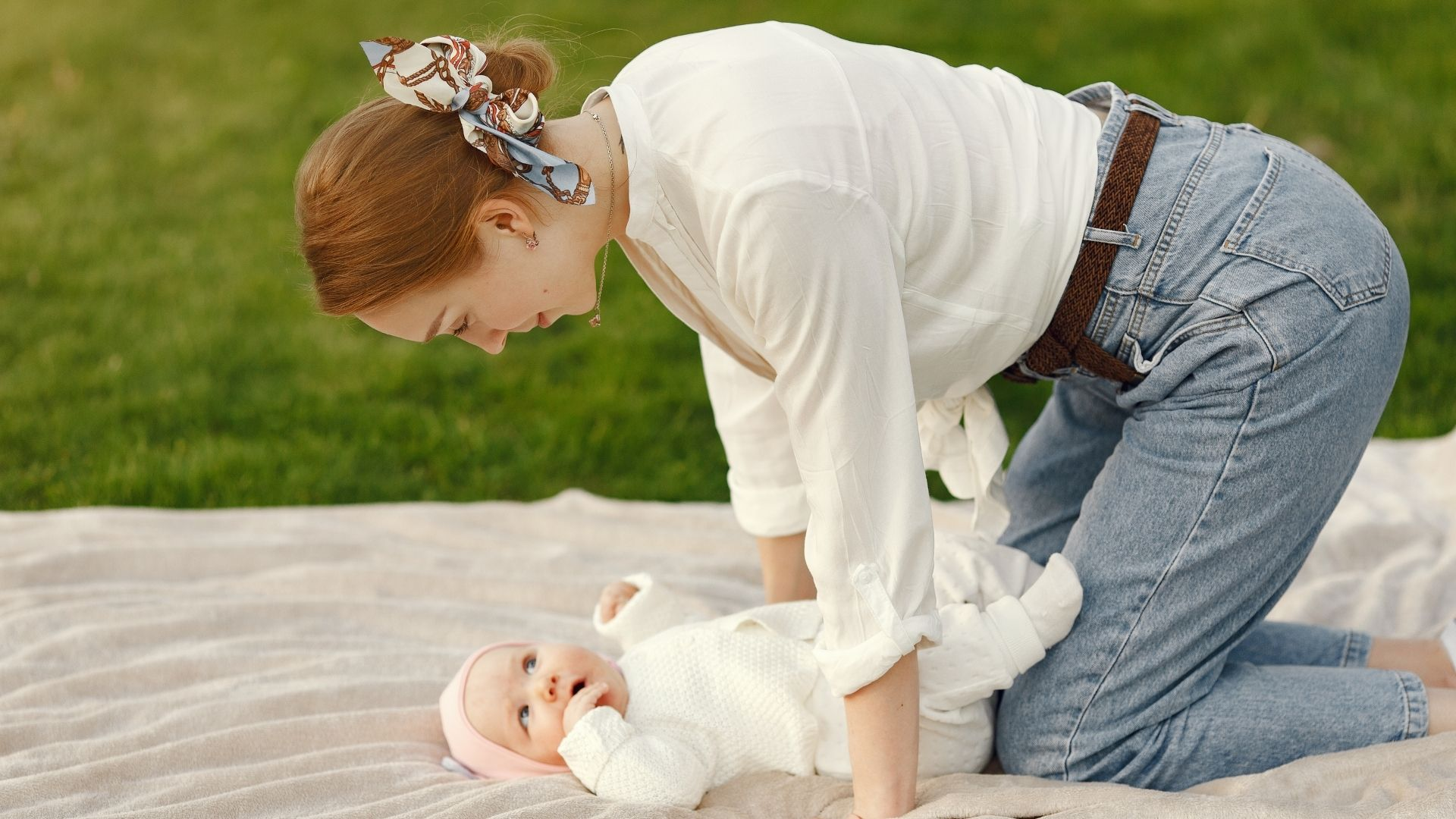 picture of a woman wearing mom jeans playing with her baby.