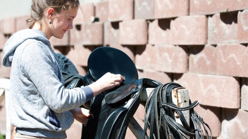 Picture of a girl cleaning her horse tack.