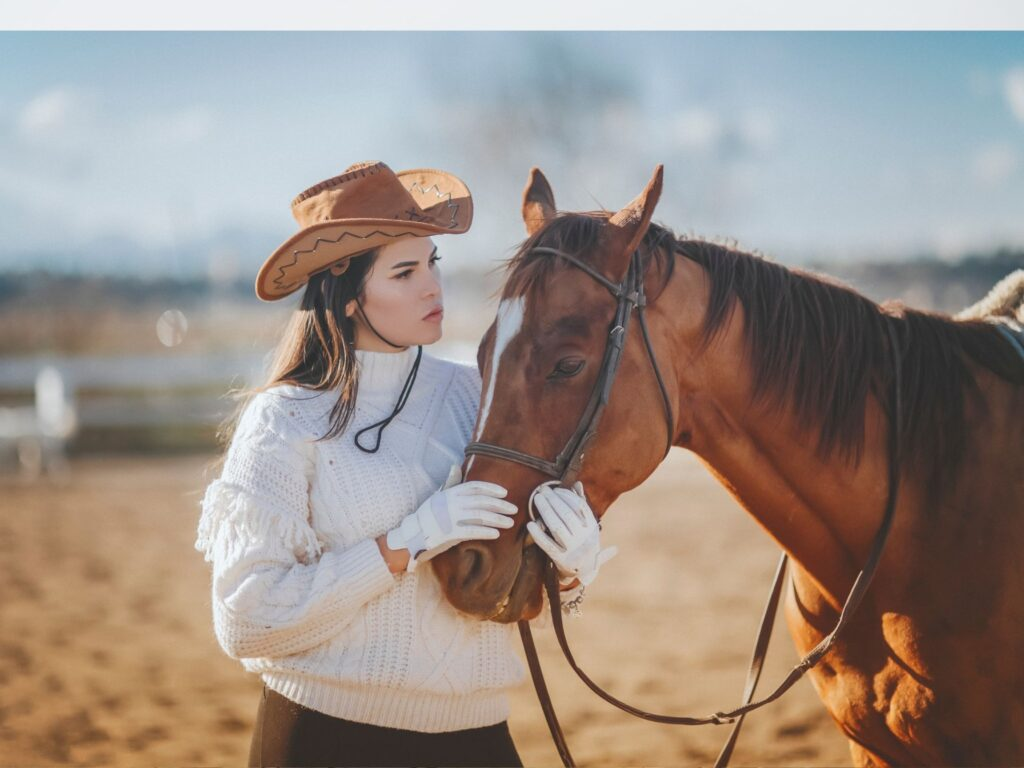 Picture of a woman wearing a cowboy hat with her horse.